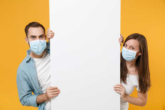 People in sterile face masks hold big white empty blank billboard isolated on yellow background studio. Epidemic rapidly spreading coronavirus 2019-ncov medicine flu virus ill sick treatment concept.