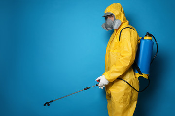 Man wearing protective suit with insecticide sprayer on blue background, space for text. Pest control Fotobehang