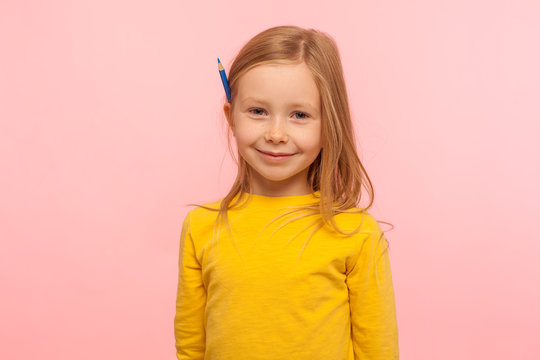 Portrait of charming adorable little girl with ginger hair holding pencil behind ear and smiling to camera, development of creative child abilities. indoor studio shot isolated on pink background