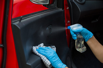 Cleansing car interior and spraying with disinfection liquid. Hands in rubber protective glove disinfecting vihicle inside for protection from virus corona disease