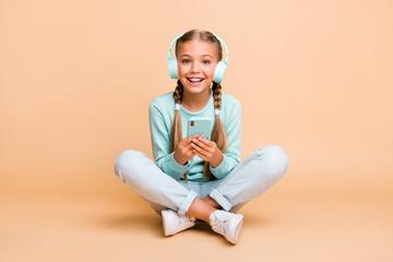 Full body photo of beautiful funny little lady enjoy listen earphones song good mood sit floor legs...