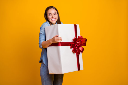 Portrait of energetic crazy girl hold hug get big white gift box with red ribbon enjoy anniversary event party wear good look clothes isolated over shine color background