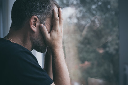portrait one sad man standing near a window