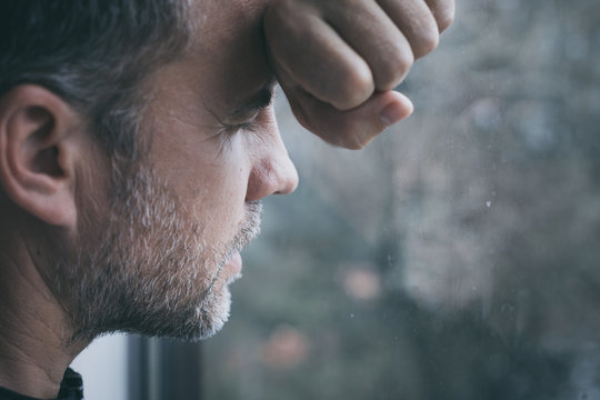 portrait one sad man standing near a window