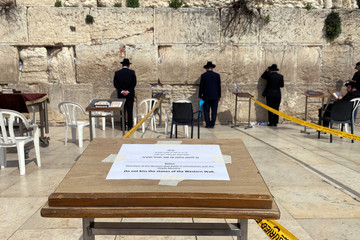 Ultra-Orthodox Jewish men pray in front of the Western Wall, Judaism's holiest prayer site, in Jerusalem's Old City as a note advice not to kiss the stones of the Western Wall display