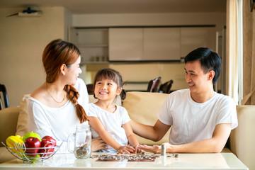 Asian family teaching their daughter saving money to piggy bank for her future education, Asian family concept