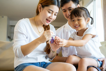 Asian mother and father sitting on sofa painting her daughter nail with happiness feeling in living room home sweet home, Asian family concept