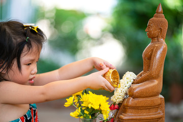 Asian girl pour water on Buddha statue for doing respected and ask for blessing in Thai Songkran festival, a famous cultural day in Thailand, Asian family Concept