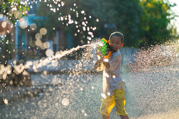 Asian children using water splash gun to their friend in very hot weather day, Songran festival is very popular festival in Thailand and Asia. Water splash, Songkran, Summer activity or Asian concept