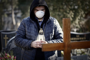 Man stands over the grave of a deceased coronavirus in the cemetery, wearing a protective mask. Fototapete