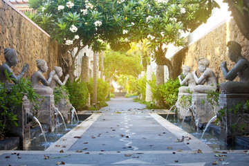 exotic Bali scenery passage with traditional architecture, fountains, sculpture, gate and foliage Wall mural
