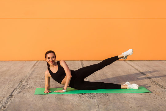 Cheerful athletic girl in tight sportswear, black pants and top, practicing yoga, doing side plank pose with leg lift, stretching muscles, training flexibility. Health care, sport activity outdoor