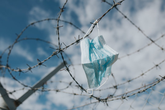 Surgical mask blown by the wind at the airport got stock on the wired fence. Representative image for coronavirus outbreak and cancelled flights.