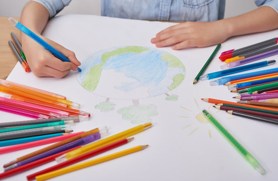 Child boy  draws  planet for earth day. Protection of enviroment, Mother Earth Day greeting and celebration. Save our planet! Concept of art learning and education, love earth , save world and unity