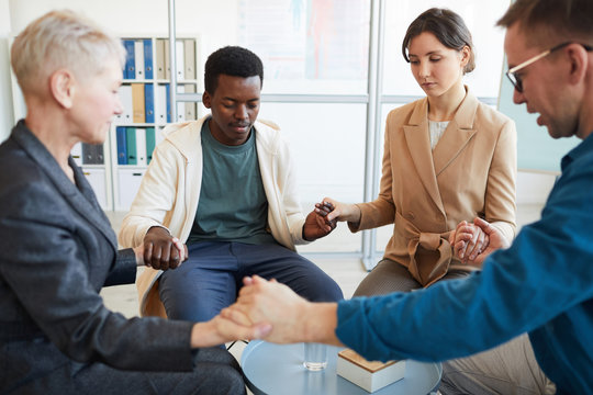 Multi-ethnic group of people holding hands in prayer while sitting in circle in support group, copy space