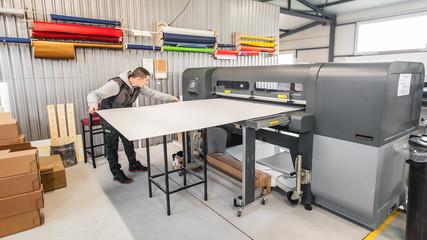 Technician operator works on large premium industrial printer plotter machine Papier Peint