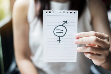 Young woman hand showing paper note with gender of LGBTQ symbol for Lesbian, Gay, Bisexual, Transgender and Queer community