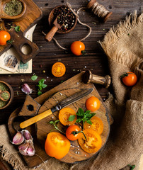 overhead shot of ripe juicy yellow tomatoes and basil on wooden boards with vintage knife on rustic table with spices, herbs, pepper, salt, garlic, sackcloth, food background process of cooking