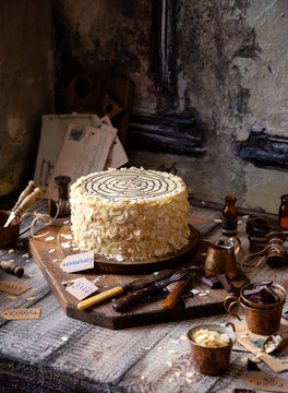 traditional hungarian cake esterhazy on wooden boards on grey wooden table with copper cups, vintage forks, almond petals opposite concrete wall