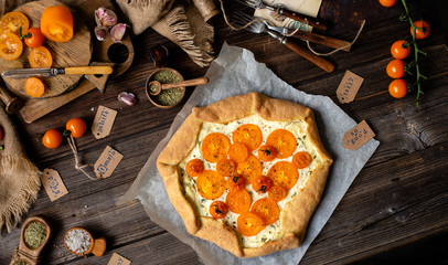 overhead shot of homemade galette, pie or vegetable pizza with white filling and yellow tomatoes, herbs and spices on rustic wooden table with sackcloth, veggies, garlic, basil