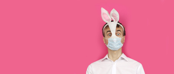banner with frightened man in mask Easter Bunny and medical mask look ahead, virus or coronavirus protection holiday