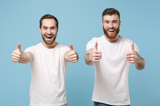 Cheerful two young men guys friends in white t-shirt posing isolated on pastel blue background. Sport leisure lifestyle concept. Mock up copy space. Cheer up support favorite team showing thumbs up.