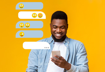 Fototapeta Millenial African American guy using smartphone for chat communication on orange background, empty space obraz