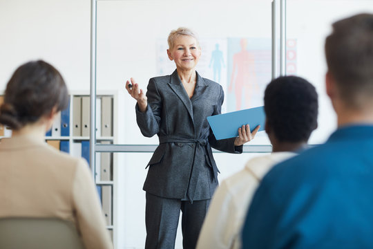 Portrait of smiling female business coach giving speech to audience during seminar, copy space