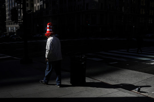 """A person wearing a hat from Dr. Seuss' children's story, """"The Cat in the Hat"""" walks across 11th Street Northwest during a morning commuter hour as Mayor Muriel Bowser declared a State of Emergency due to the coronavirus disease (COVID-19) in Washington"""