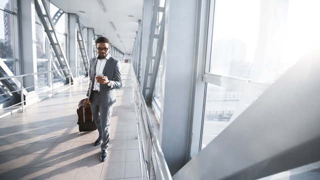 African American Entrepreneur Texting Walking With Suitcase In Airport, Panorama