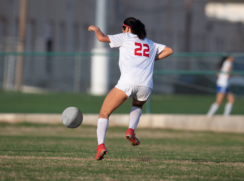 High school girl competing in a soccer match in south Texas