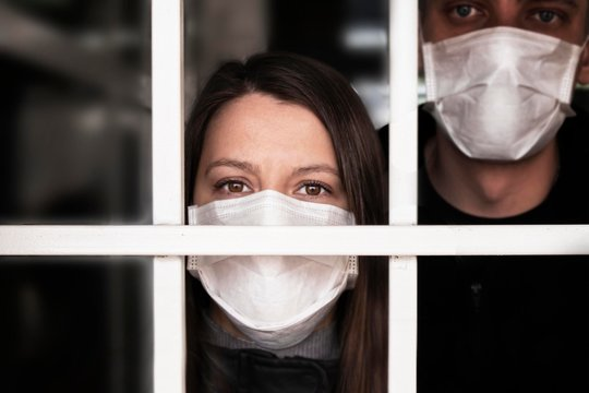 A woman in a mask , looking intently at the camera. Quarantine and isolation of patients with covid coronavirus 2019. Isolation grid, incarceration and illness. . Fear in the eyes and uncertainty