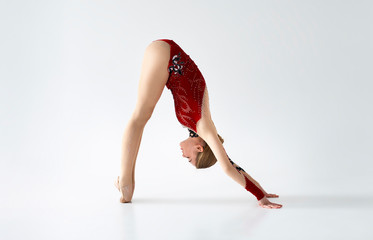 Professional gymnast in bright sports suit stretching before performance on white background