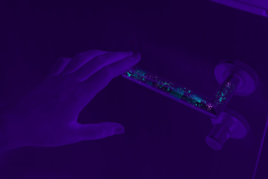 Bacteria, germs and Coronavirus revealed with ultraviolet UV light on dirty door handle surface
