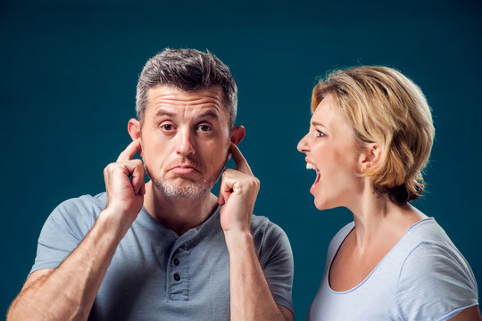A portrait of angry couple. Wife screaming at her husband. People and emotions concept