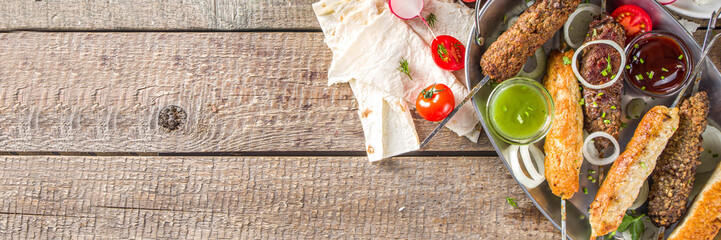 Foto op Textielframe Kip Summer bbq party. Shish kebab on a stick, from ground beef and chicken meat. Lula kebab, traditional Caucasian asian dish. With various sauces, spices and tomatoes, grey stone background