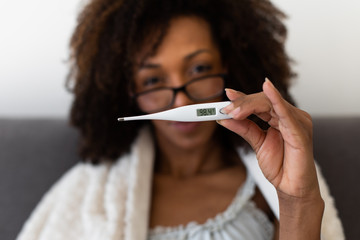 Woman shows a thermometer with normal body temperature after overcoming a virus infection and...