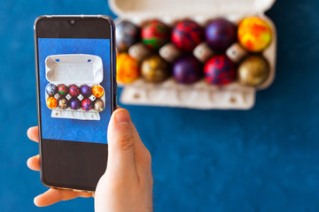 Holidays, tradition, technology and people concept - close up of man hands with smartphone taking picture of colored easter eggs.
