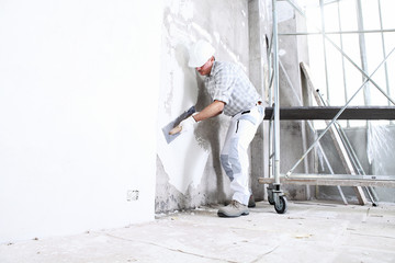 plasterer man at work with trowel plastering the wall of interior construction site wear helmet and protective gloves, scaffolding on background and copy space on white wall