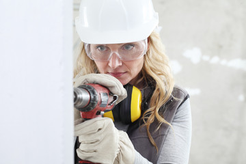 woman contruction worker using cordless drill driver making a hole in wall, builder with safety hard hat, hearing protection headphones, gloves and protective glasses, close up portrait Wall mural