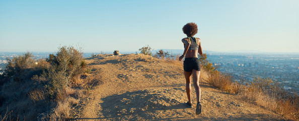 Fototapeta fit african american woman running at runyon canyon with los angeles in background obraz