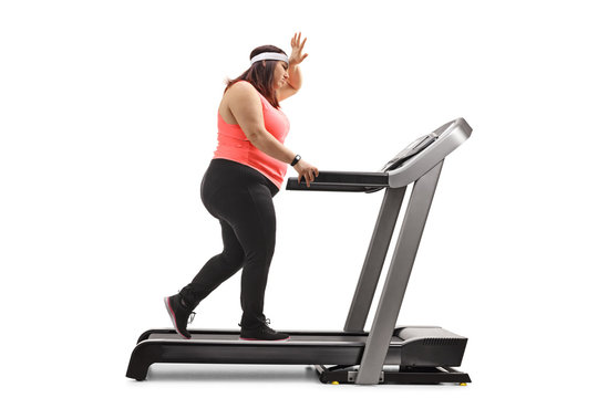 Overweight woman exercising on a treadmill and holding her forhead