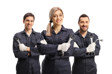 Team of a one female and two male mechanics holding working tools Wall mural