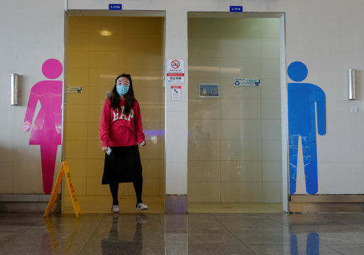 A woman wearing a protective face mask and goggles, due to the coronavirus outbreak, walks in an airport in Phuket