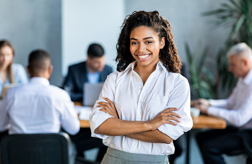 Black Businesswoman Smiling At Camera Posing Standing In Modern Office