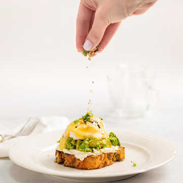 Avocado egg benedict with cream cheese Philadelphia. Poached eggs on healthy pumpkin bread toast with hollandaise sauce. Sauce is pouring from a spoon