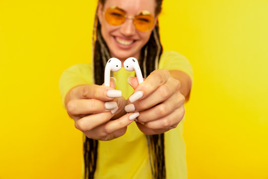 Listening music on airpods. Woman in the yellow studio with white airpods
