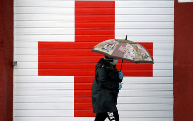A woman wearing a mask and gloves walks past Red Cross offices during a partial lockdown in the Asturian town of Oviedo.