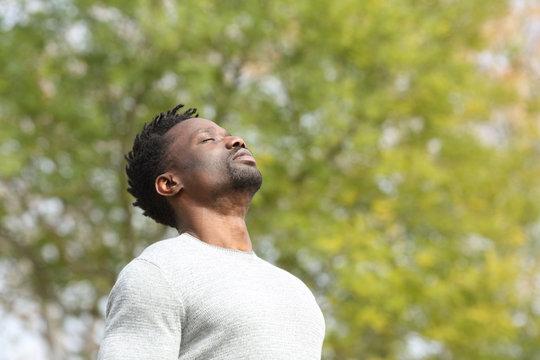 Black serious man breathing fresh air in a park