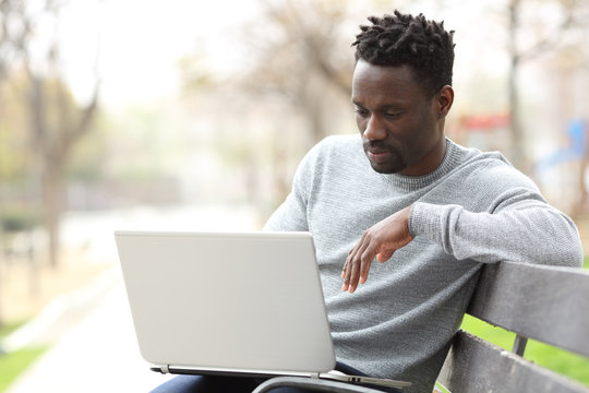 Serious black man using a laptop in a park